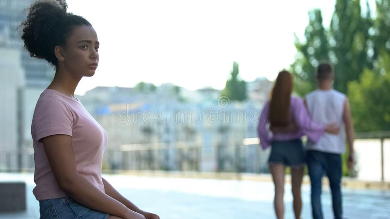 Mixed-race female student feeling alone, couple in love walking nearby, puberty royalty free stock photos