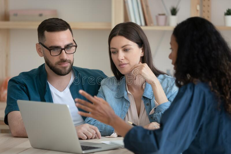 Mixed race financial advisor showing presentation on laptop to clients. stock photos