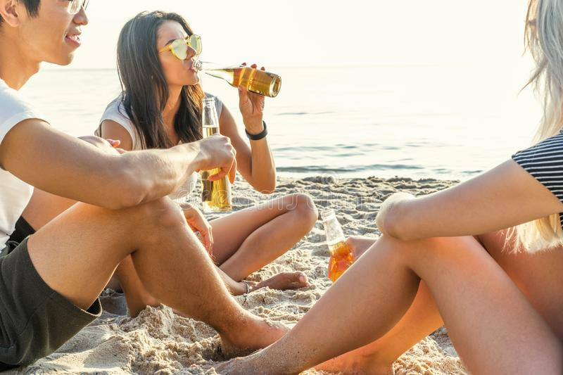 Mixed race friends having fun at the beach. Group of happy young people sitting together at the beach talking and royalty free stock photography