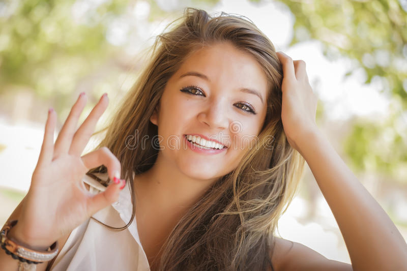 Mixed Race Girl Portrait with Okay Hand Sign Outdo stock photography