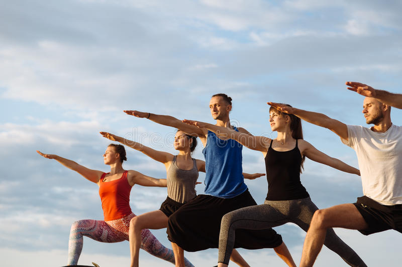 Mixed race group of people exercising yoga healthy lifestyle fitness warrior poses stock photo