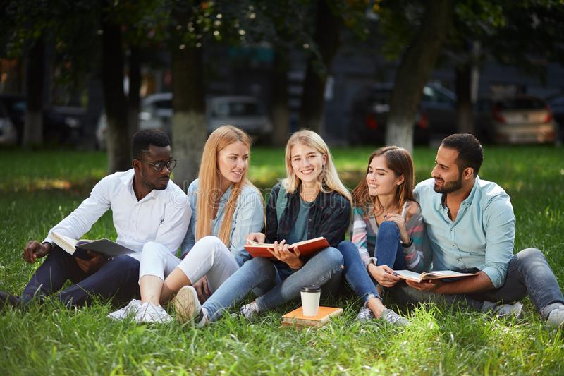 Mixed-race group of students sitting together on green lawn of university campus royalty free stock images