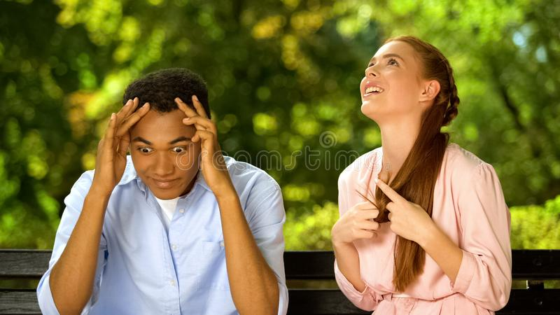 Mixed-race guy shocked by too talkative and annoying girl during first date. Stock photo royalty free stock photos