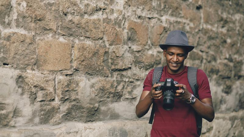 Mixed race happy tourist man taking photo on his dslr camera standing near famous building in Europe. Mixed race happy tourist man taking photo on his dslr royalty free stock images
