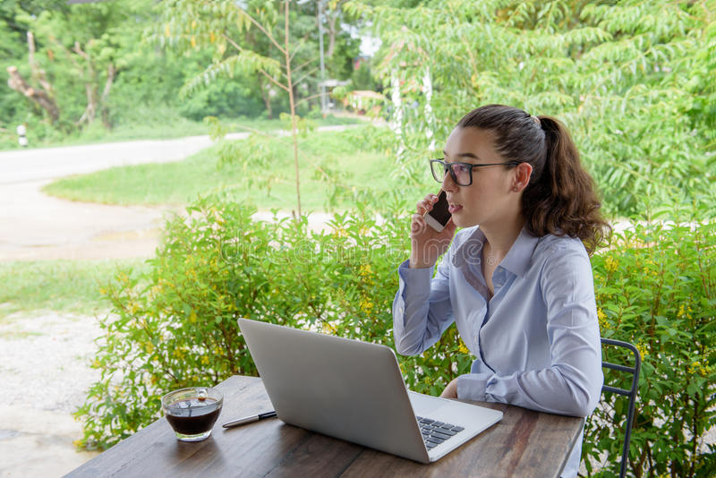 Mixed-race long hair young woman talking on smart phone and using laptop while siting and work out door. stock image