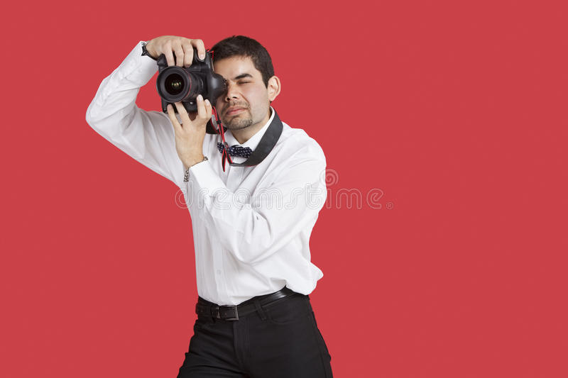 Mixed race man taking picture with digital camera over red background stock image