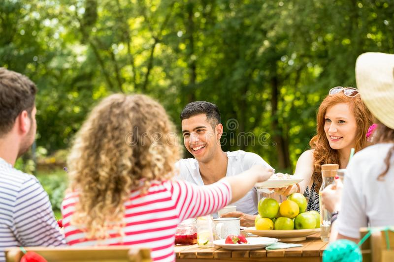 Mixed-race man and his friends sitting in the yard during a casual, summer meeting. Mixed-race men and his friends sitting in the yard during a casual, summer royalty free stock images