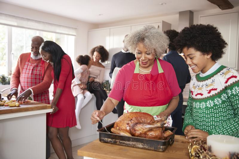 Mixed race, multi generation family gathered in kitchen before Christmas dinner, grandmother and grandson preparing roast turkey i. N foreground royalty free stock images