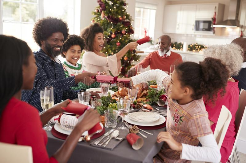 Mixed race, multi generation family having fun pulling crackers at the Christmas dinner table stock photos