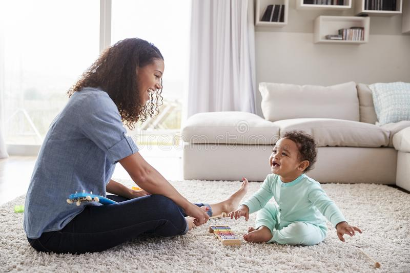 Mixed race mum and toddler son playing in sitting room royalty free stock photos