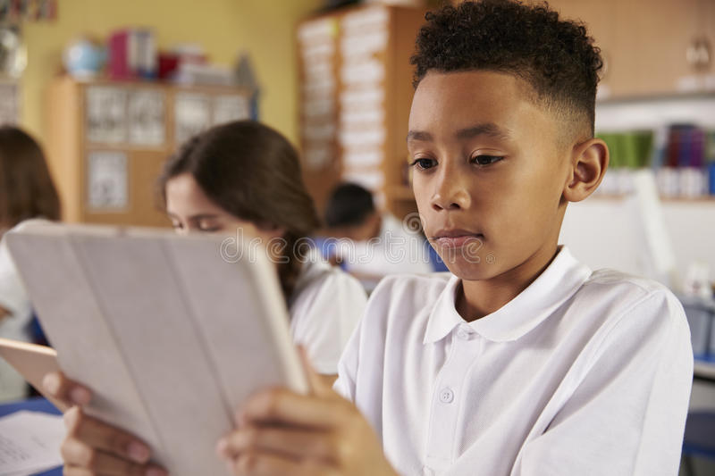 Mixed race primary school boy using tablet computer in class royalty free stock images