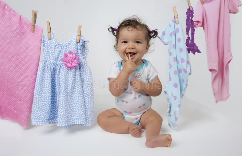 Baby playing with clothespin in laundry line royalty free stock images