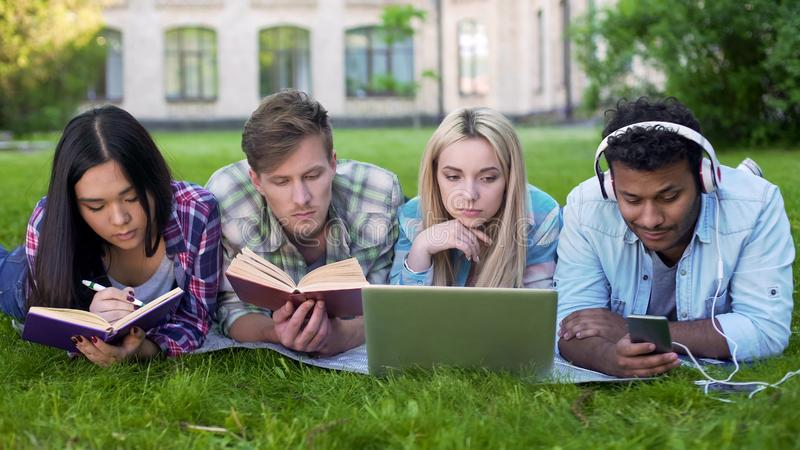 Mixed-race students lying on grass and preparing for exams, university education stock photo