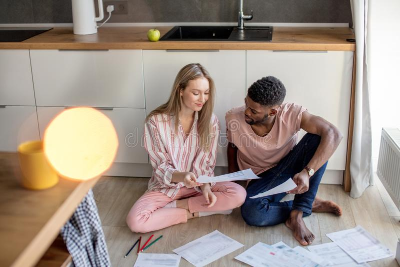 Mixed-race students sitting together on kitchen floor at home prepare to exams royalty free stock photos
