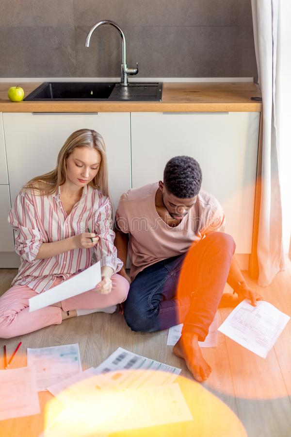 Mixed-race students sitting together on kitchen floor at home prepare to exams stock photos