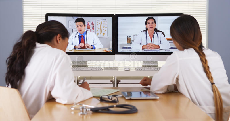Mixed race team of medical doctors having a video conference royalty free stock photo