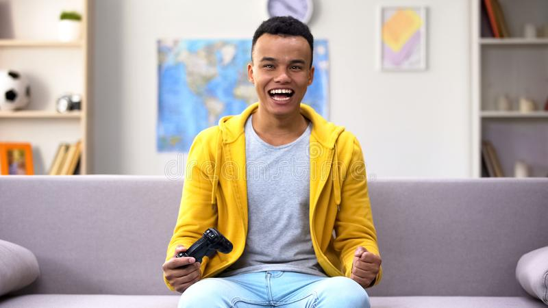 Mixed-race teen boy playing video game rejoicing victory, leisure time at home stock images