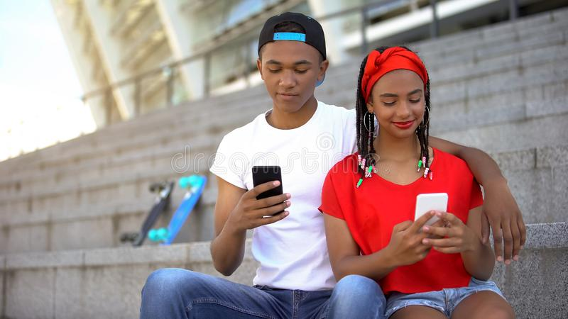 Mixed-race teens scrolling social network on smartphones instead communication royalty free stock images