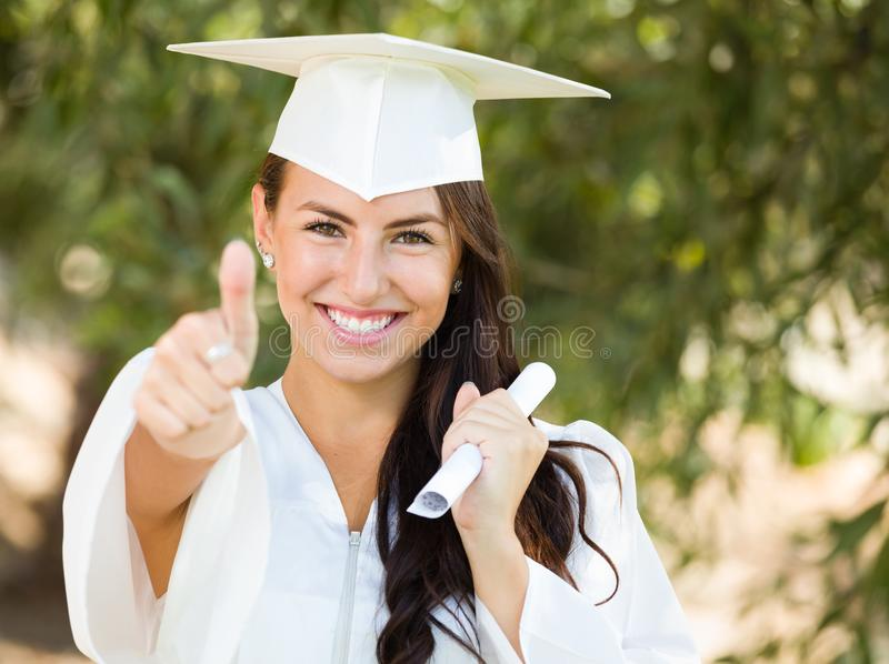 Mixed Race Teen Girl Gives Thumbs Up at Graduation In Cap and Gown royalty free stock photo