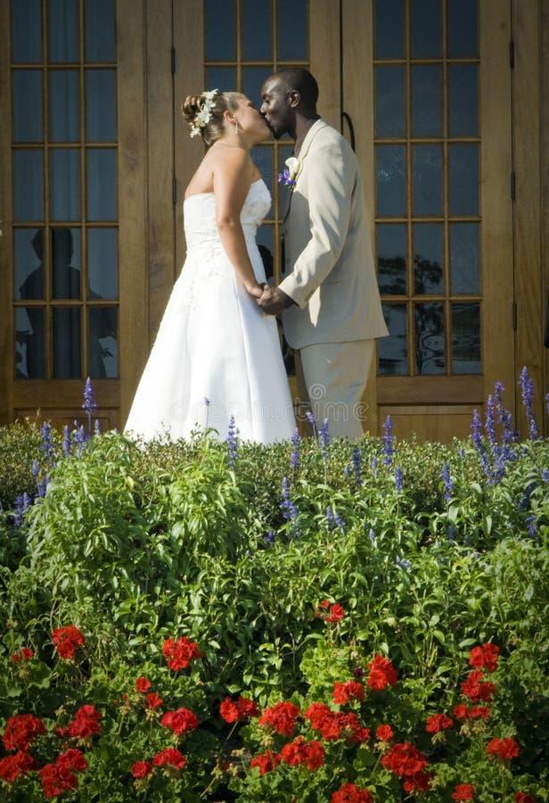 Mixed race wedding couple kiss stock images