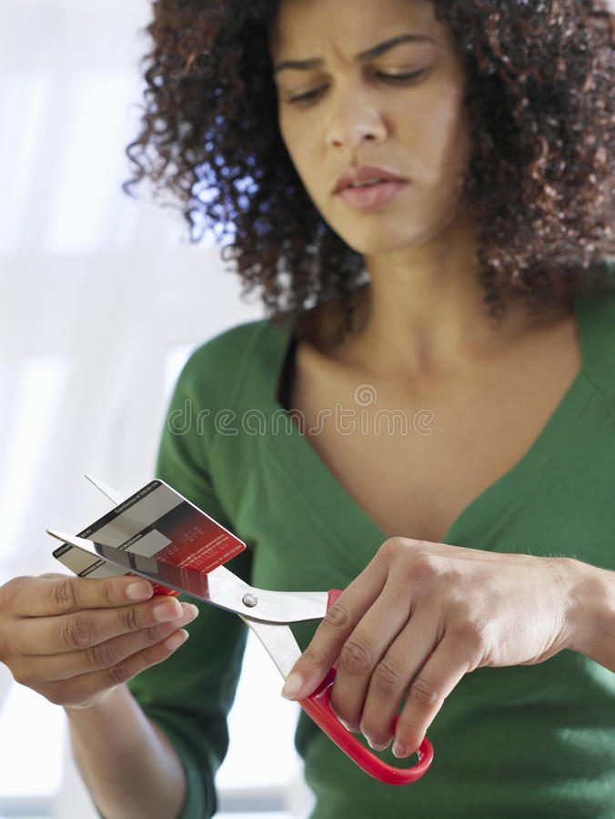 Mixed Race Woman Cutting Credit Card royalty free stock images
