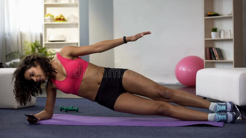 Mixed race woman doing side plank and using mobile phone, taking selfie photo royalty free stock photography