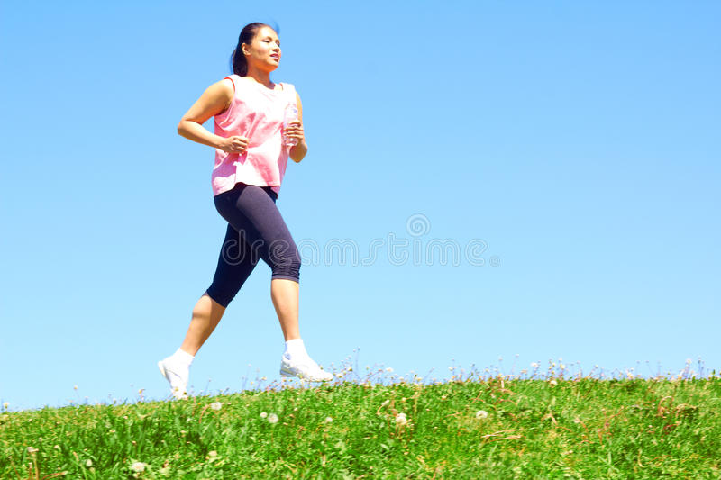 Mixed Race Woman Jogging. Sporty mixed race woman jogging. Color image, copy space, asian ethnicity female running with green grass and blue sky royalty free stock images