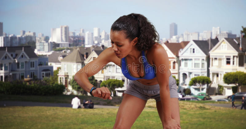Mixed race woman runner looking at her fitness watch at the park.  stock image