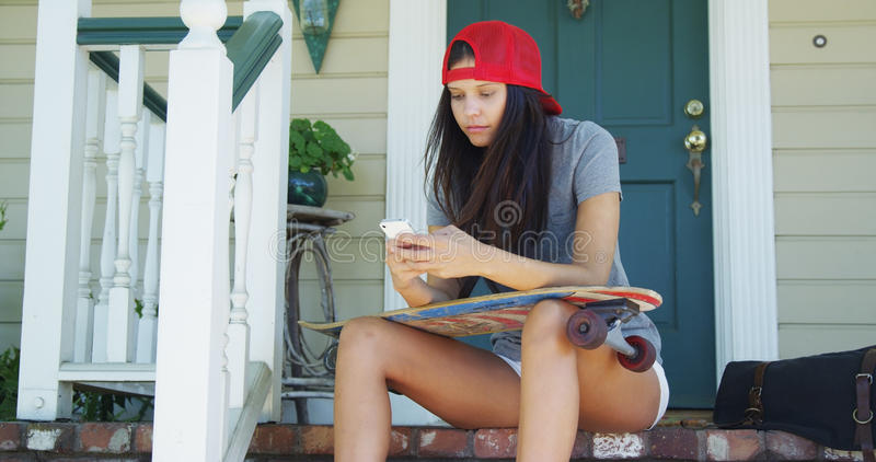Mixed race woman sitting on porch with skateboard texting. Outside royalty free stock image