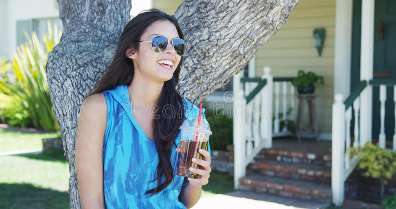 Mixed race woman standing by tree drinking iced tea. Cute mixed race woman smiling by tree outdoors royalty free stock photography
