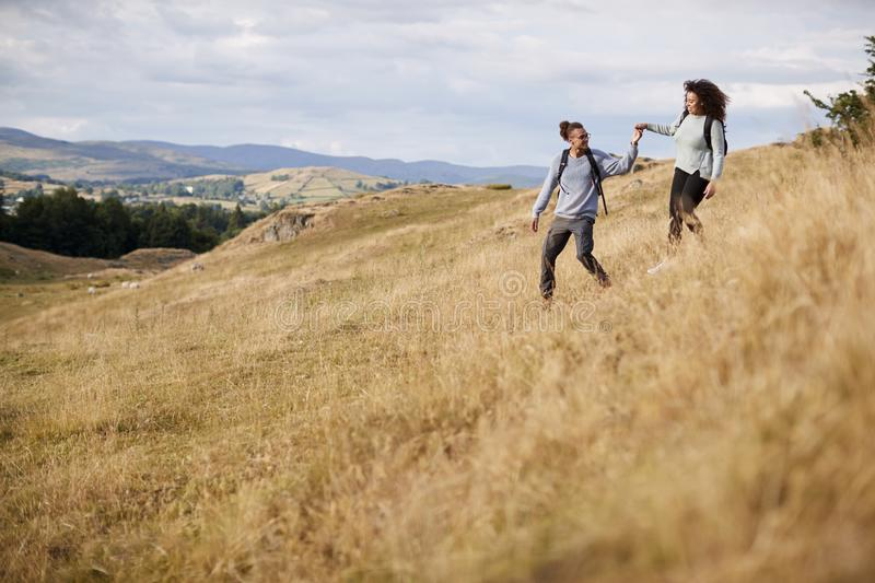 Mixed race young adult couple holding hands while walking walking down a hill during a mountain hike royalty free stock image