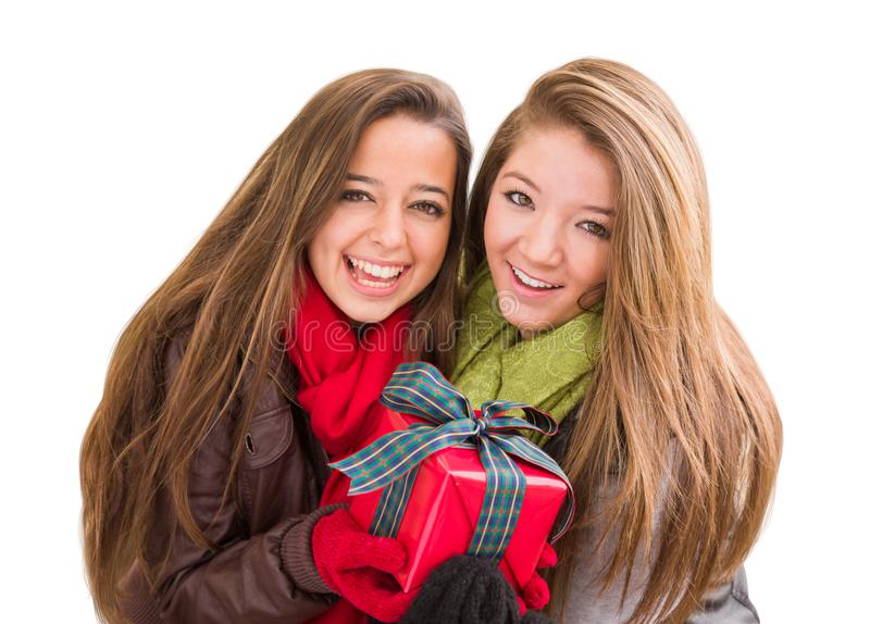 Two Mixed Race Teenaged Females Holding A Christmas Gift Isolated. Mixed Race Young Adult Females Holding A Christmas Gift Isolated on a White Background royalty free stock images