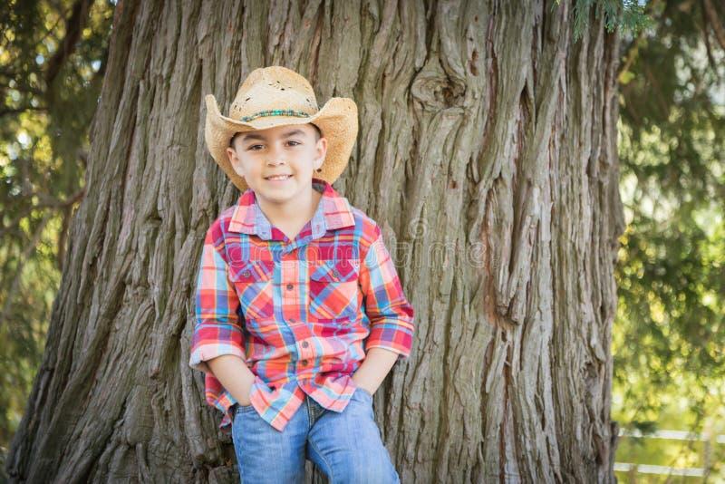 Cute Mixed Race Young Boy Wearing Cowboy Hat Standing Outdoors. Mixed Race Young Boy Wearing Cowboy Hat Standing Outdoors stock photos