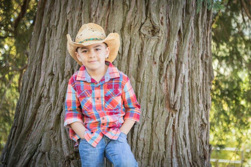 Mixed Race Young Boy Wearing Cowboy Hat Standing Outdoors. Mixed Race Young Boy Wearing Cowboy Hat Standing Outdoors by a Tree royalty free stock photos