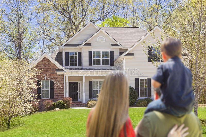 Mixed Race Young Family Looking At Beautiful Home royalty free stock images