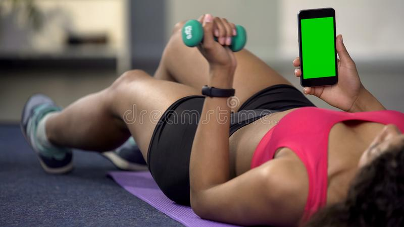 Mixed race young female using phone with green screen, flexing arm with dumbbell stock photography