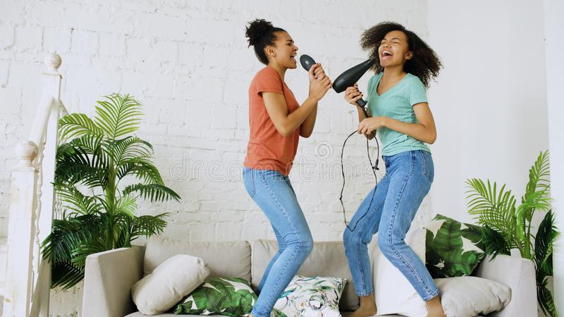 Mixed race young funny girls dance singing with hairdryer and comb jumping on sofa. Sisters having fun leisure in living royalty free stock photos