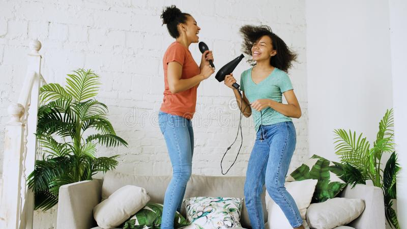 Mixed race young funny girls dance singing with hairdryer and comb jumping on sofa. Sisters having fun leisure in living royalty free stock images
