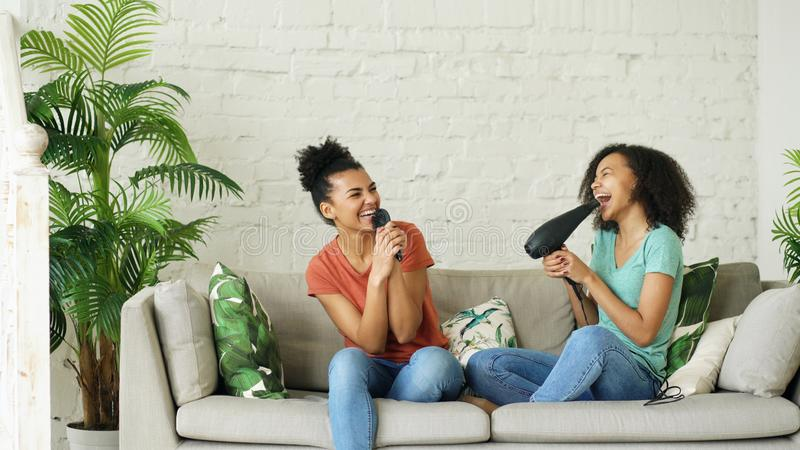 Mixed race young funny girls dance singing with hairdryer and comb sitting on sofa. Sisters having fun leisure in living stock images
