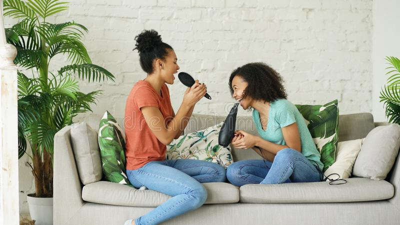 Mixed race young funny girls dance singing with hairdryer and comb sitting on sofa. Sisters having fun leisure in living royalty free stock images