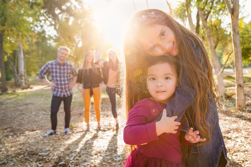 Mixed Race Young Girl Sisters Outdoors with Family Behind royalty free stock photo