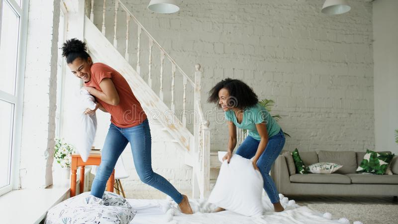 Mixed race young pretty girls jumping on bed and fight pillows having fun at home royalty free stock images