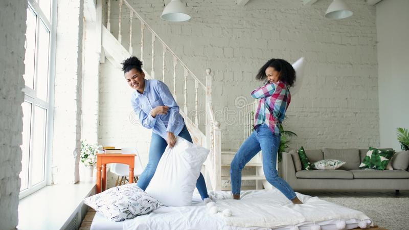 Mixed race young pretty girls jumping on bed and fight pillows having fun at home stock photography