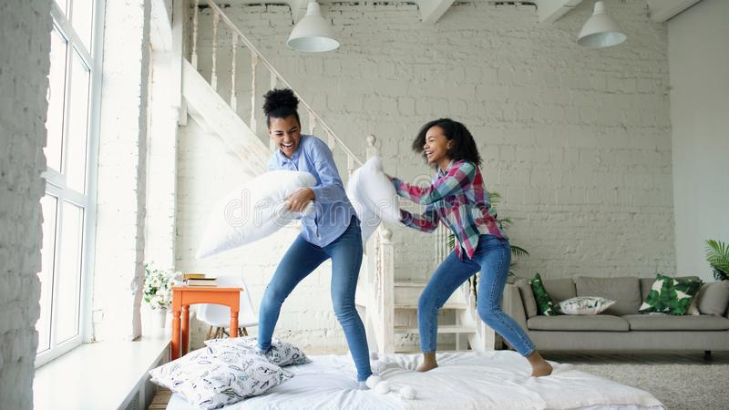 Mixed race young pretty girls jumping on bed and fight pillows having fun at home stock images
