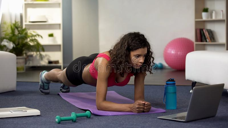 Mixed race young woman doing online workout in front of laptop, exercising royalty free stock photo