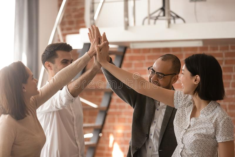 Mixed raced smiling office workers celebrating good work result. royalty free stock image
