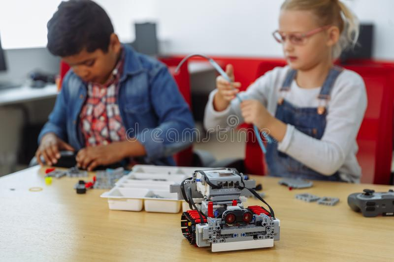 Mixed Racial group of School kids sitting at class with diy robot, stem education concept. stock photo