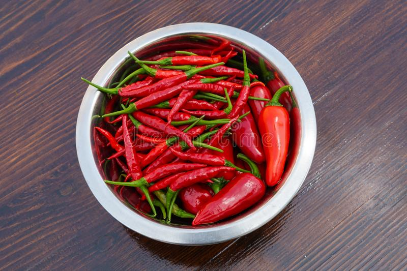Mixed red hot chili peppers in bowl on a wooden table royalty free stock photo