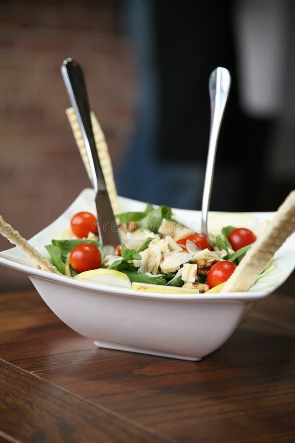 Mixed salad. A bowl of fresh mixed salad on a wooden table royalty free stock photos