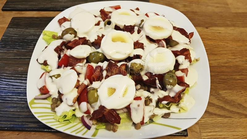 Mixed salad of eggs, olives, onion, dried tomatoes, cherry tomato and bacon. stock photography